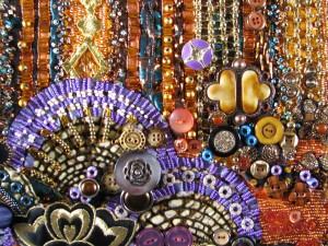 Detail of an art quilt with a beaded fan motif.